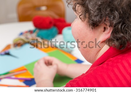a mentally disabled woman with a lot of handicraft - stock photo