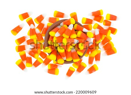 A mess of Halloween candy corn kernels on a white background with a small bowl in the center. - stock photo