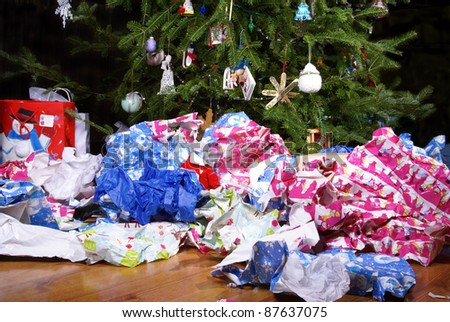 A Mess of Wrinkled Wrapping Paper Scattered Under the Christmas Tree - stock photo