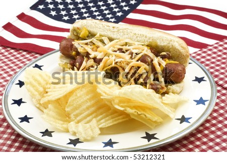 A messy chili and cheese hotdog on a plate served with potato chips and an American flag background, selective focus - stock photo