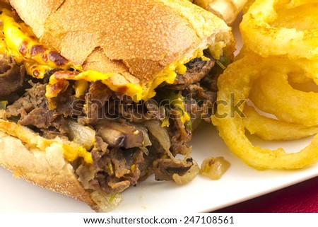 A messy Philly Cheesesteak with onions peppers and mushrooms, onion rings on the side - stock photo