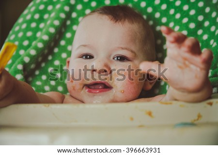 A messy ten month old baby boy sitting in his highchair during meal time