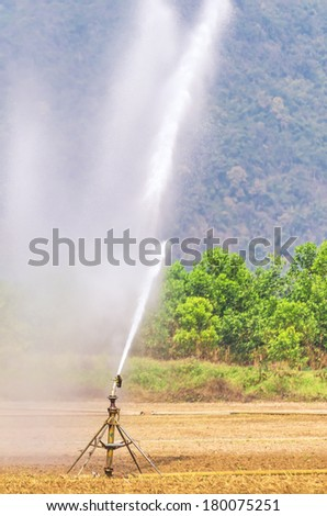 A metal automatic water sprinkler in the vast field, Nozzles are watering the field