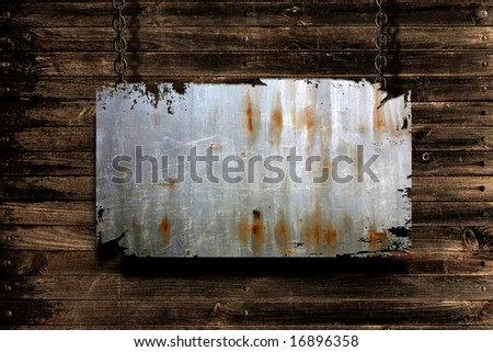 A metal banner held with chains on a grungy wood background - room for copy on the banner - stock photo