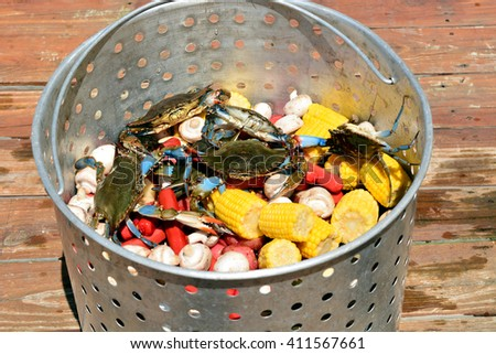 A metal basket of live blue crabs and crawfish, with sausage, potatoes, corn on the cob, mushrooms and garlic, sitting on a wooden dock, ready for boiling.