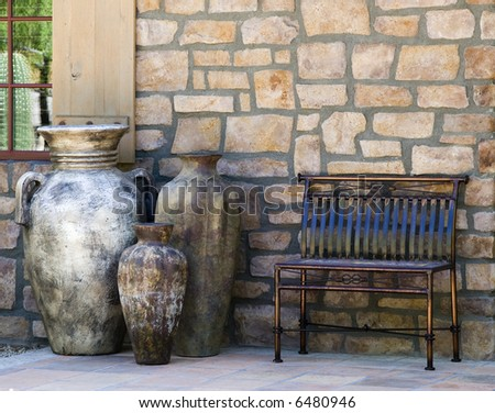 A metal bench and a trio of large, decorative urns front the stone wall of a home in the American southwest. - stock photo