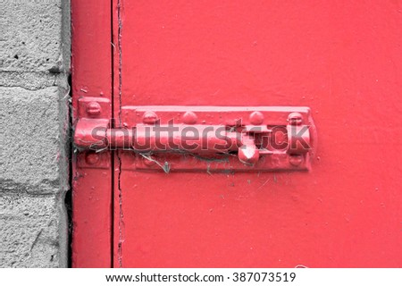 A metal bolt locks on a red painted door - stock photo