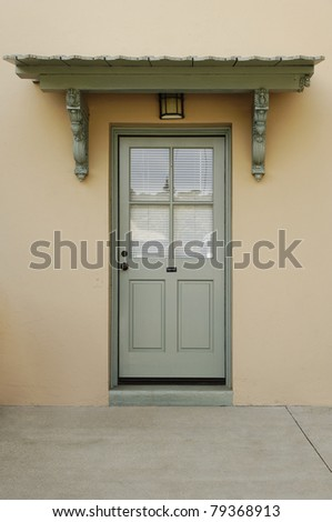 A metal book door with four glass panes is set under an arbor. The shades on the door are drawn closed. Vertical shot. - stock photo