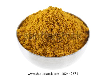 A metal bowl of spicy Curry Powder, main ingredient to cook Asian curry, isolated on white background
