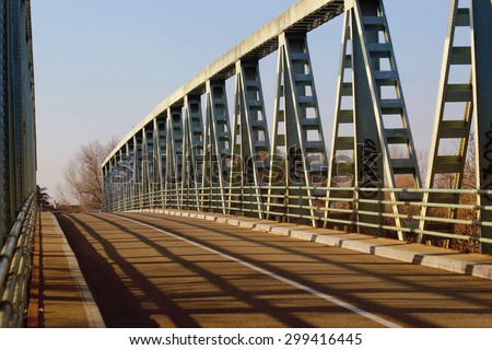 A metal bridge that crosses a river on the sunse - stock photo