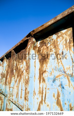 A metal container that is rusted and blue.