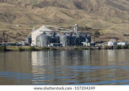 A metal grain silo storage facility on a river - stock photo