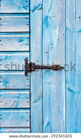 A metal hinge on a blue wooden door - stock photo