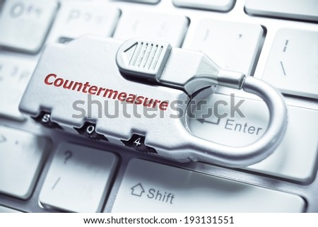 a metal lock with password on computer keyboard - countermeasure concept for computer security - stock photo