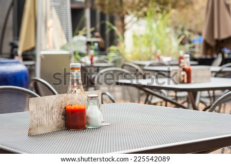 A metal outdoor restaurant table with a ketchup bottle, salt shaker, and menu. An outdoor heater and other tables are in the background.  - stock photo