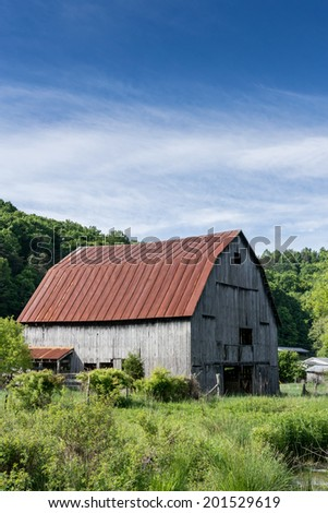 A metal roofed barn with simple wooden walls sits along a creek in rural Virginia