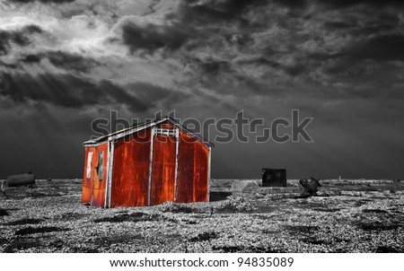 a metal shed rusts away on the shingle beach at dungeness, south east england. A black and white image with a colour pop on the corroded shack itself. - stock photo