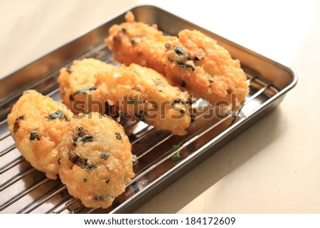 A metal tray of crispy, golden fried foods. - stock photo