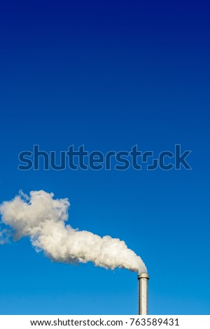 A metallic chimney giving off a heavy cloud of white smoke against a deep blue sky.