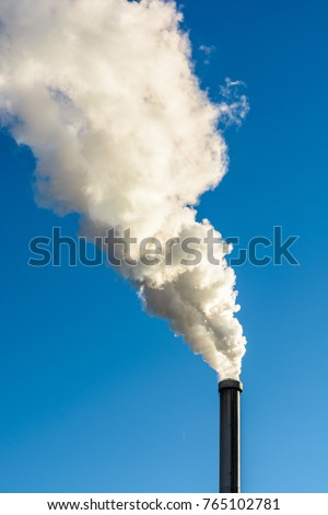 A metallic chimney spitting out a heavy cloud of white smoke against a deep blue sky.