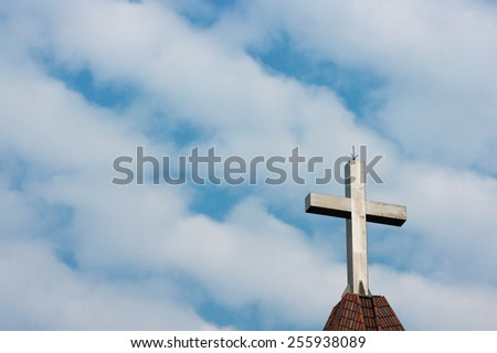 A Metallic Cross on Top of A Church Against Blue And Cloudy Sky. - stock photo