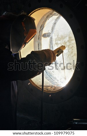 A metalworker welding a metal barrel - stock photo