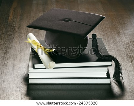 A metaphorical graduation background with a view of a academic hat, diploma and a stack of books on a wooden surface. - stock photo