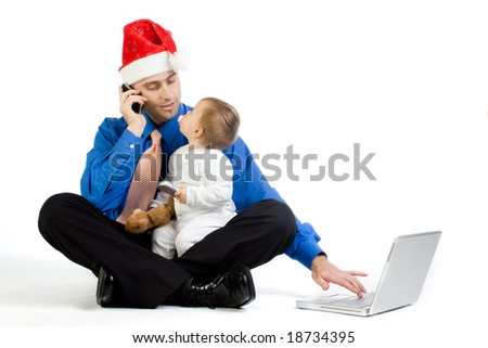 A metaphorical image of a man wearing a santa hat with his baby girl, juggling in the roles of being a businessman and a father. - stock photo