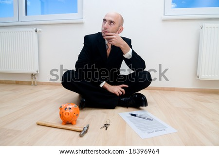 A metaphorical image showing a businessman with his piggybank checking if he has enough savings to buy the new house he is sitting in. - stock photo