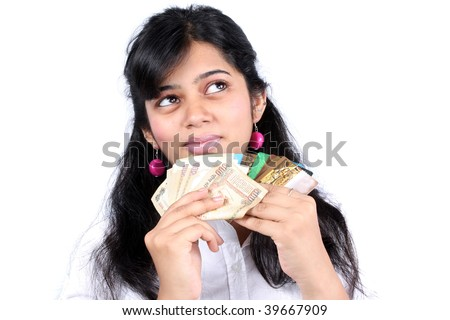 A metaphorical portrait of an Indian teenage girl holding cash and credit cards, on white studio background. - stock photo