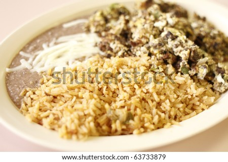A Mexican breakfast consisting of beans, rice, and machaca or eggs with shredded beef.