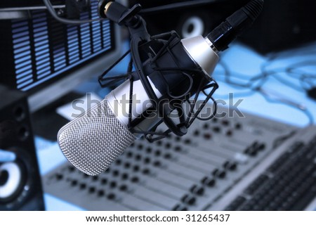 A mic in front of the control panel in broadcasting studio - stock photo