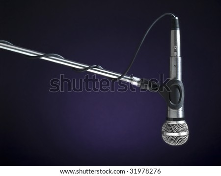 A microphone on a boom over a blue background. - stock photo