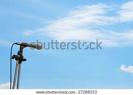 A microphone on a stand over the sky - stock photo