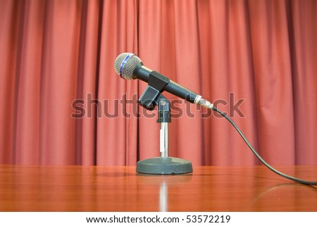 A microphone on stage over a red background. - stock photo