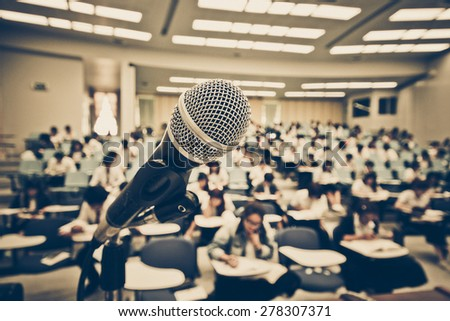 A microphone with blur background of many students learning - stock photo