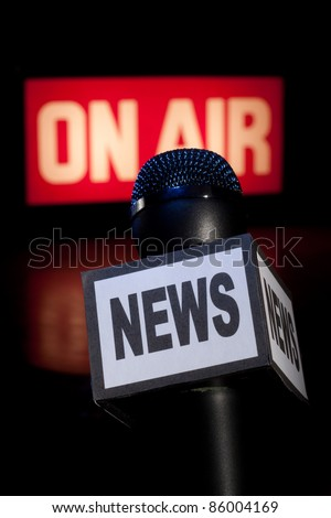 A Microphone with the word News on the side and on-air radio and television broadcast sign in the background with copy space. Vertical image. - stock photo