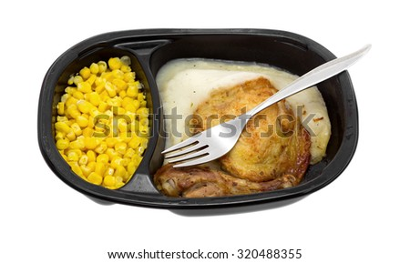 A microwaved TV dinner of roasted chicken with mashed potatoes and corn in a black plastic tray with a fork isolated on a white background. - stock photo