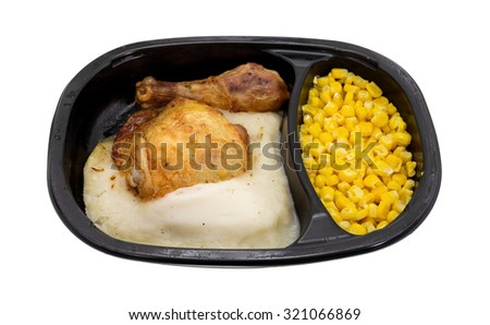 A microwaved TV dinner of roasted chicken with mashed potatoes and corn in a black plastic tray isolated on a white background. - stock photo