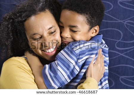 A mid adult African American woman affectionately hugging her young son. Horizontal shot. - stock photo
