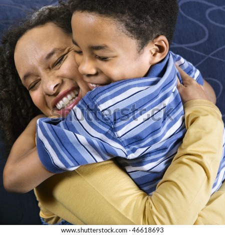 A mid adult African American woman affectionately hugs her young son. Square shot.