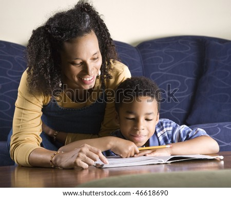 A mid adult African American woman sits on a couch while helping her young some with his homework. Horizontal shot. - stock photo
