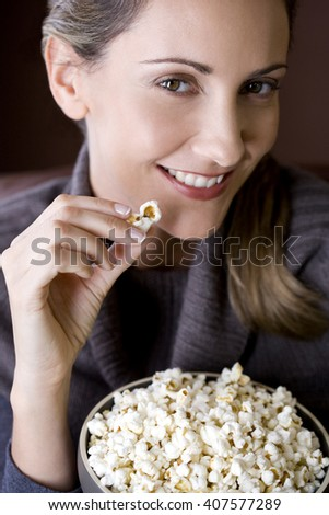 A mid adult woman eating popcorn - stock photo