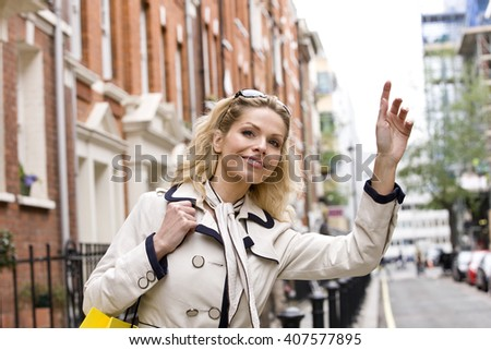 A mid adult woman hailing a taxi - stock photo