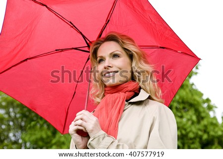 A mid adult woman holding a red umbrella