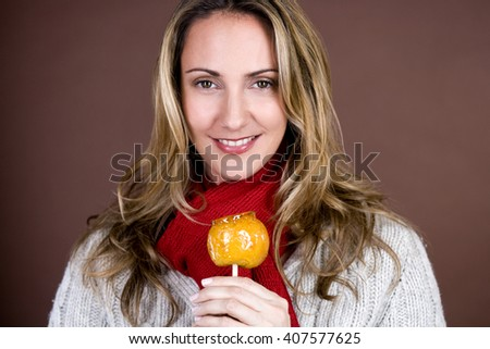 A mid adult woman holding a toffee apple, smiling - stock photo