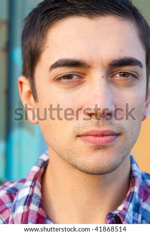 A mid-20s man is outside of a train car with graffiti modeling a plaid western button up shirt. - stock photo