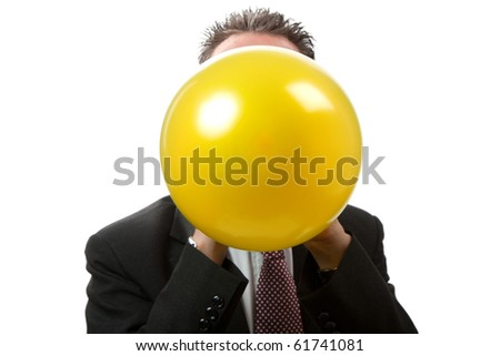 A mid thirties business man blowing up a yellow balloon.  Facing camera.   Studio isolated on a white background. - stock photo