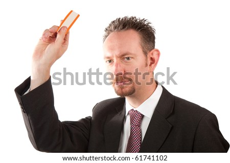 A mid thirties business man holding up a ticket.  The man is wearing a suit and tie and has spiky hair and a goatee beard.  Studio isolated on a white background. - stock photo