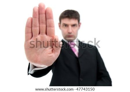 A mid thirties businessman in a black suit indicates STOP with his hand.  Differential focus on the hand.